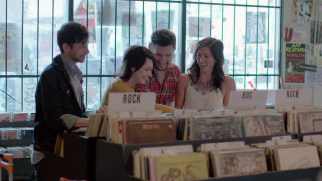 Group of friends walk into Austin record store and look through vintage vinyl albums