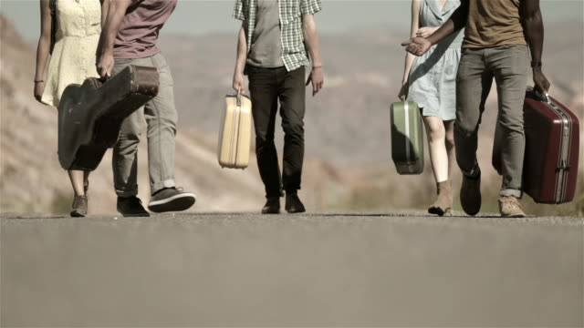 Group of friends walk up desert road carrying luggage