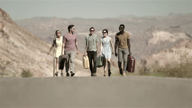 Group of friends walk up scenic desert road carrying luggage
