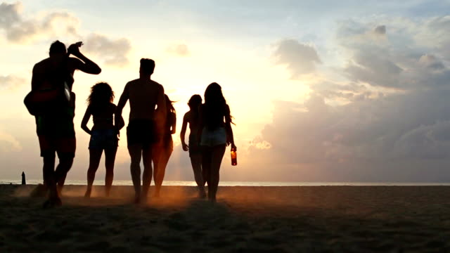 Group of friends walking on the beach at sunset