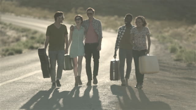 Group of friends walking with luggage down lonely desert road