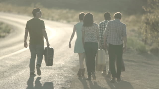Group of friends walking with luggage up lonely desert road