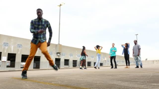 MS LA Group of friends watching man dancing in empty parking lot