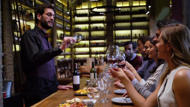 group of friends wine tasting at wine bar with a sommelier guiding the class - gourmet stock videos & royalty-free footage