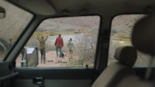 group of friends with dog pile out of car to check out scenic camp site on the colorado river. - attività all'aperto video stock e b–roll