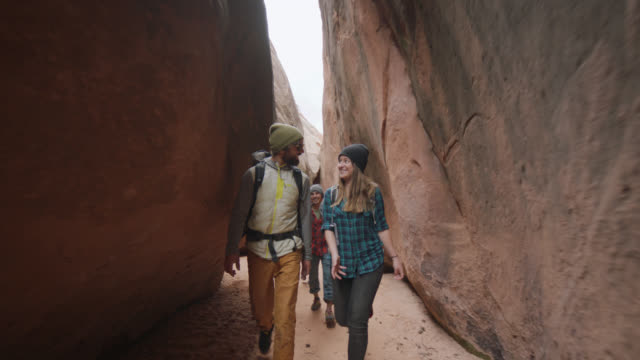 SLO MO. Group of friends with dog smile at each other as they walk through narrow slot canyon on Moab hiking trip.
