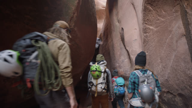 group of friends with dog walk down through narrow slot canyon on moab hiking trip. - canyon stock videos & royalty-free footage
