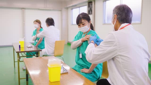 stockvideo's en b-roll-footage met groep eerstelijns gezondheidswerkers die zich in vaccinatiecentrum laten vaccineren - menselijke arm