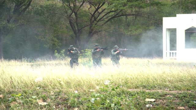 grupp av fullt utrustade och beväpnad soldat är i en okända områden - fältslag bildbanksvideor och videomaterial från bakom kulisserna