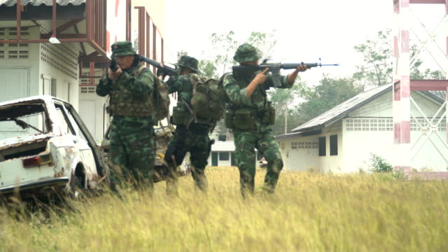 group of fully Equipped and Armed Soldiers  patrol in unknown area.