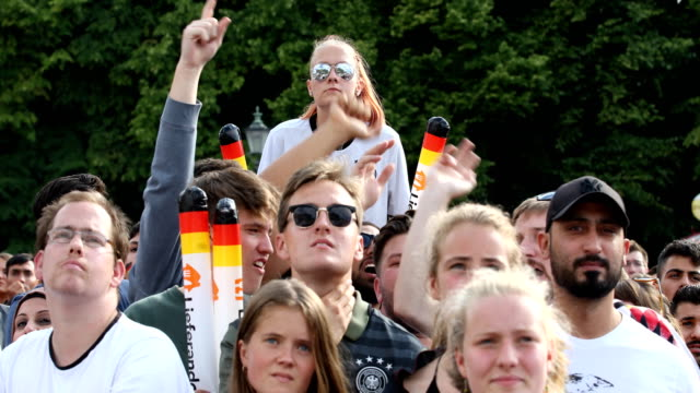 A group of German fans are singing hopeful 'Deutschland schieß ein Tor' They are waving with plastic sticks In the background is sitting a young...