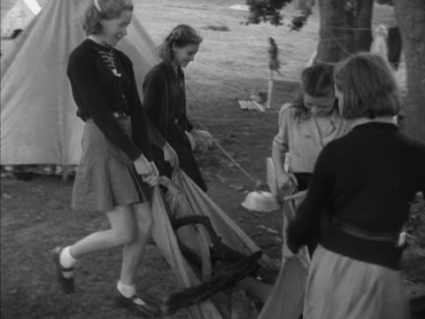 vidéos et rushes de group of girl guides carry logs for a fire at a camping site. - guide