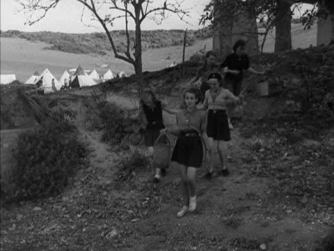 vidéos et rushes de group of girl guides collect water from a tap at a camping site. - guide