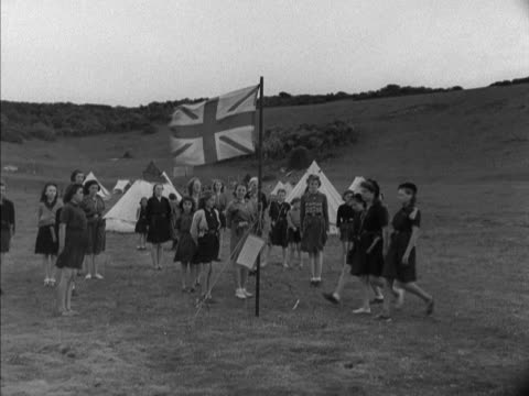 stockvideo's en b-roll-footage met group of girl guides stand to attention as the union flag is lowered at a camping site. - alle vlaggen van europa