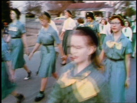 1957 pan group of girl scouts in uniforms walking in parade / feature - guide stock videos & royalty-free footage