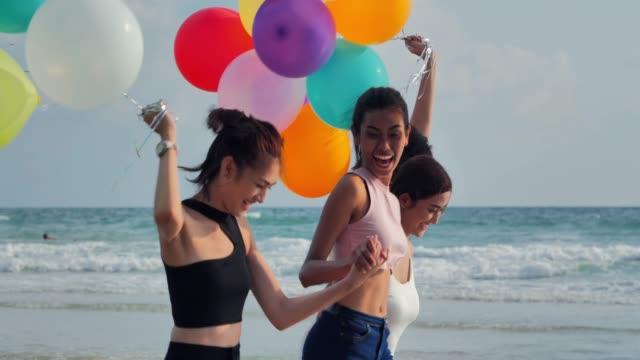 vidéos et rushes de groupe de copines fonctionnant sur la plage avec un ballon sur un fond d'un ciel bleu. bonheur amis amusement sur la plage sous la lumière du soleil du coucher du soleil en été jour ensoleillé. vacances-istock - groupe d'objets
