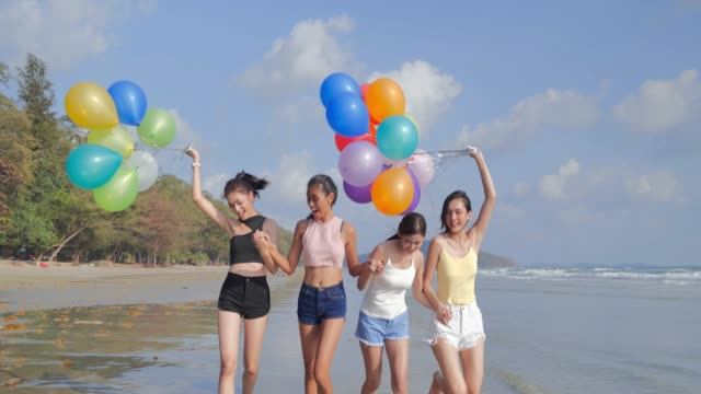 group of girlfriends walking on the beach with a balloon against a background of a blue sky.happiness friends fun on the beach under sunset sunlight in summer sunny day.vacations - istock - gruppo di oggetti video stock e b–roll