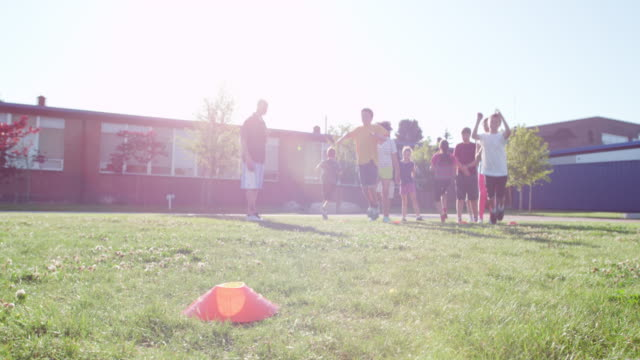 MS SLO MO Group of girls and boys in relay race on grass field in front of school
