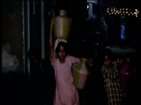 Group of girls carry buckets of water through slum area in early morning hours India