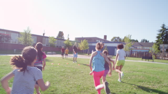 vidéos et rushes de ms ts slo mo group of girls racing on grass field towards coach at finish line - aire de jeux