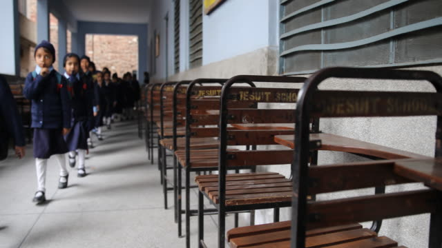 Group of girls walking in line and making the silent sign with their hands walk down the school's hall with chairs on the right side