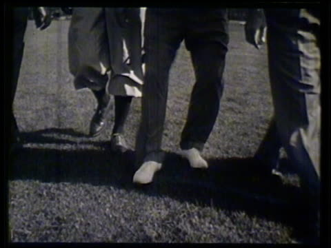 stockvideo's en b-roll-footage met group of golfers & bing crosby walking on golf course, crosby stomping on opponent's golf ball, stepping into path of opponent's putt, opponent... - bing crosby