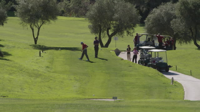 ha ls group of golfers waiting at tee, young man teeing off towards camera, red r3d 4k - golf stock-videos und b-roll-filmmaterial