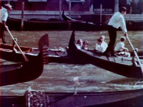 VENICE ITALY Group of Gondoliers rowing gondolas w/ passengers on canal Iconic Venetian boat oarsman tourists tourism