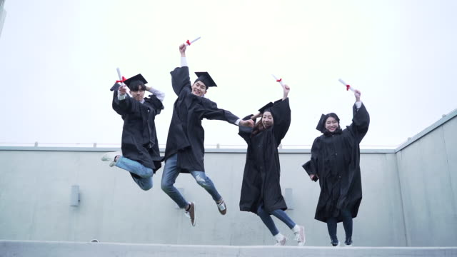 group of graduates jumping in a row - korean ethnicity stock videos & royalty-free footage