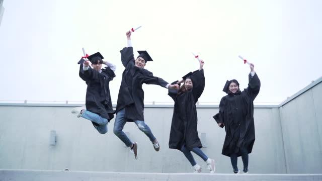 vídeos y material grabado en eventos de stock de group of graduates jumping in a row - coreano oriental