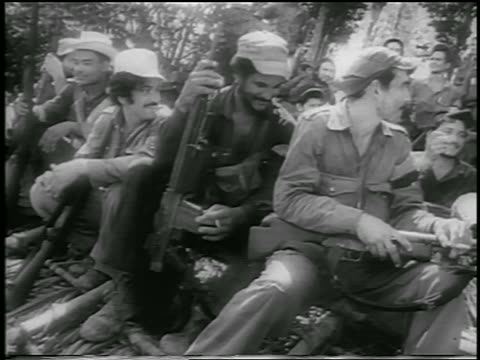 B/W 1959 group of guerrilla soldiers with guns sitting on ground outdoors / Cuba / newsreel