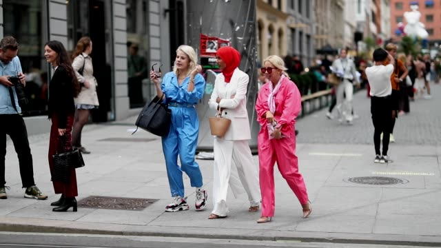 A group of guests wearing a blue and a pink overall and a guest wearing white wide leg pants and blazer are seen during Oslo Runway SS19 on August 15...