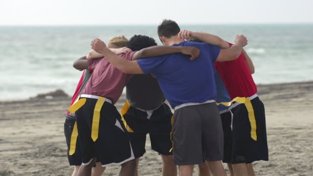 vidéos et rushes de a group of guys playing flag football on the beach. - slow motion - amitié masculine