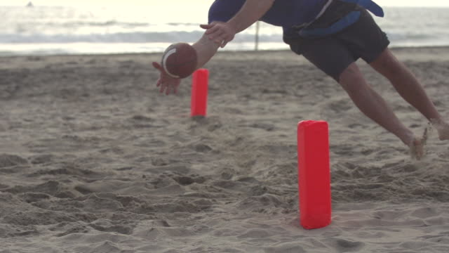 a group of guys playing flag football on the beach. - super slow motion - filmed at 240 fps - gefangen stock-videos und b-roll-filmmaterial