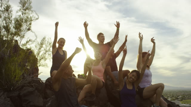 Group of happy adults together on top of a hill cheering.