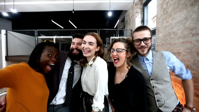 Group of happy co-workers making selfie and silly faces