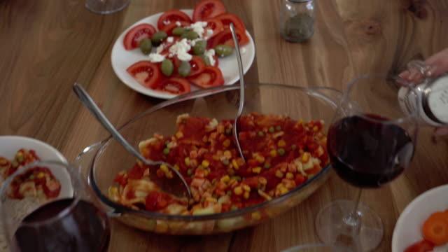 Groep gelukkige vrienden genieten in een maaltijd in de eetkamer en roosteren met rode wijn.