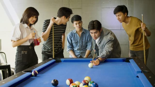 Group of happy friends having fun playing billiard at office together after work