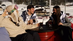 Group of happy friends in restaurant, outdoors at a ski resort drinking mulled wine and fun talk.