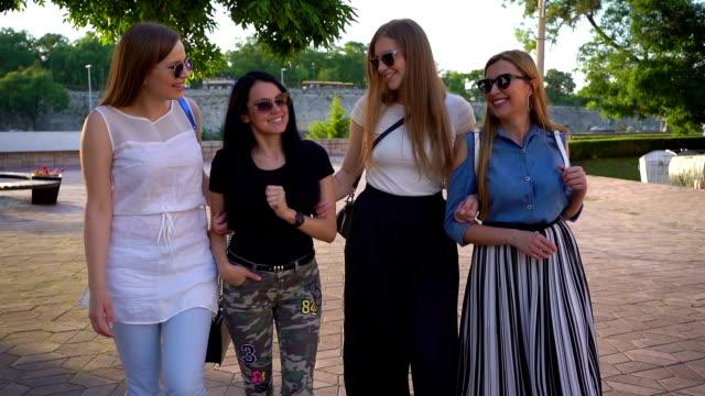 屋外を歩く幸せな女の子のグループ - 談笑する点の映像素材/bロール