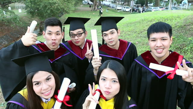 group of happy international students in mortar boards and bachelor gowns with diplomas taking a selfie by small camera outdoors. education, graduation, technology and people concept. - international match stock videos & royalty-free footage