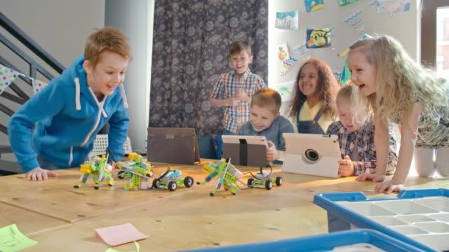 vídeos de stock, filmes e b-roll de group of happy kids playing with robot toys - stem assunto