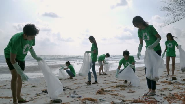 vídeos de stock e filmes b-roll de group of happy volunteers with garbage bags cleaning area on the beach.volunteerism,charity, cleaning, people and ecology concept - green