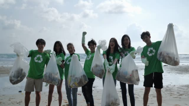 vídeos de stock e filmes b-roll de group of happy volunteers with garbage bags cleaning area on the beach.volunteerism,charity, cleaning, people and ecology concept - organização sem fins lucrativos