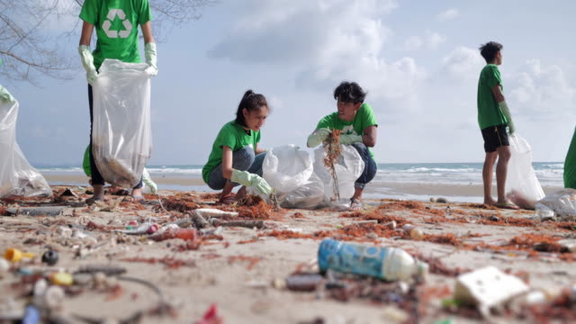 vídeos de stock e filmes b-roll de group of happy volunteers with garbage bags cleaning area on the beach.volunteerism,charity, cleaning, people and ecology concept.volunteerism - organização sem fins lucrativos