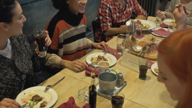 group of happy young people eating in a restaurant and talking to each other. - lunch stock videos & royalty-free footage