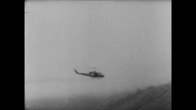 Group of helicopters silhouetted against the sky / rockets leave helicopters and fire into the Vietnamese jungle / pilots view of land targets / CU...