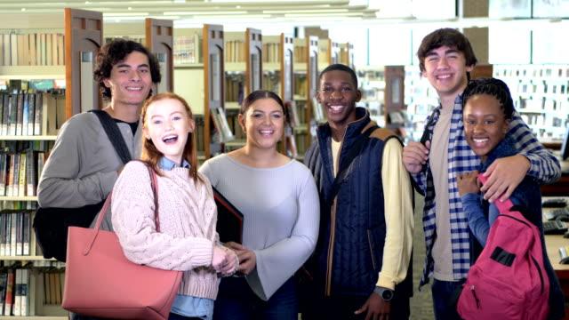 vidéos et rushes de groupe d'étudiants de lycée conversant dans la bibliothèque - 14 15 years