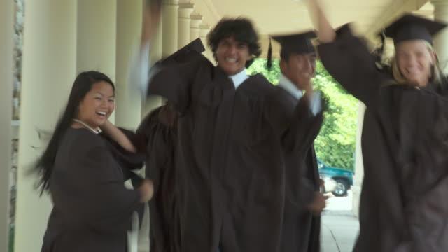stockvideo's en b-roll-footage met ms, group of high school students wearing graduation gowns running along school walkway, richmond, virginia, usa - mortelplank