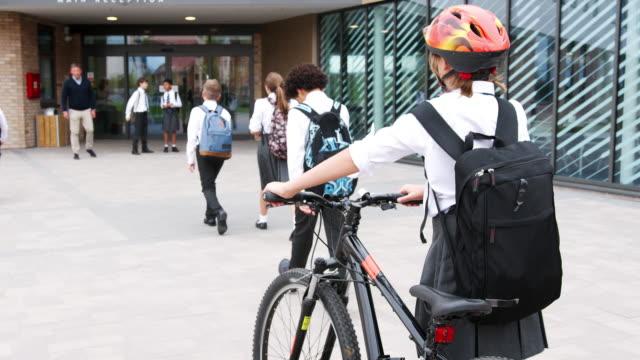 Groep van middelbare scholieren dragen van Uniform aankomen op School wandelen of paardrijden fietsen